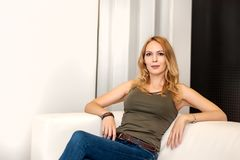 Herrliche blonde Frau, die auf weißem Sofa sitzt Stockbilder
