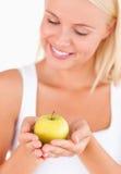 Herrliche blonde Frau, die einen Apfel anhält Lizenzfreie Stockbilder