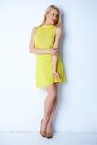 Herrliche blonde Frau, die im gelben Kleid aufwirft Stockbilder