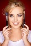 Herrliche blonde Frau, die Kosmetikbürsten hält Lizenzfreies Stockfoto