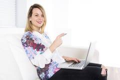 Herrliche blonde Frau, die zu Hause auf einer weißen Couch stillsteht und einen Laptop verwendet Lizenzfreie Stockbilder