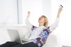 Herrliche blonde Frau, die zu Hause auf einer weißen Couch stillsteht und einen Laptop verwendet Stockbilder