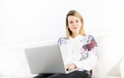 Herrliche blonde Frau, die zu Hause auf einer weißen Couch stillsteht und einen Laptop verwendet Lizenzfreie Stockfotos
