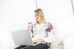 Herrliche blonde Frau, die zu Hause auf einer weißen Couch stillsteht und einen Laptop verwendet Stockbild