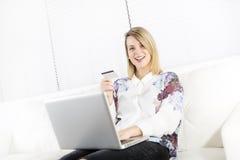 Herrliche blonde Frau, die zu Hause auf einer weißen Couch stillsteht und einen Laptop verwendet Stockfotos