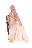 Herrliche blonde Frau in einem rosa Kleidersitzen Stockbilder