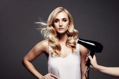Herrliche blonde Frau in einem Studio mit Haartrockner Lizenzfreies Stockbild