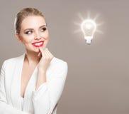 Herrliche blonde Frau mit Glühlampensymbol Lizenzfreie Stockbilder