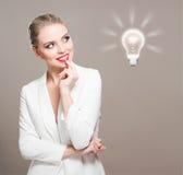 Herrliche blonde Frau mit Glühlampensymbol Stockfotografie