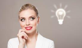 Herrliche blonde Frau mit Glühlampensymbol Stockfotos