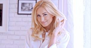 Herrliche blonde Frau, welche die Kamera betrachtet Lizenzfreie Stockfotos