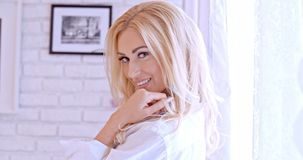 Herrliche blonde Frau, welche die Kamera betrachtet Stockfoto