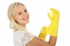 Herrliche blonde Hausfrau in den gelben Latex-Handschuhen Stockbild