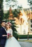 Herrliche blonde junge Braut und reizend Bräutigam, die bei Sonnenuntergang aufwirft Lizenzfreies Stockfoto