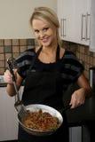 Herrliche blonde kochende Dame Stockfotografie