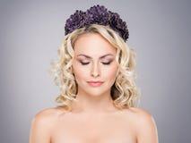 Herrliche blonde mit den geschlossenen Augen, die eine purpurrote Blume tragen, krönen Stockfotografie