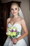 Herrliche blonde sexy Braut im weißen Kleid, das Hochzeit bouque hält Lizenzfreie Stockbilder