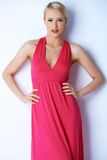 Herrliche blonde sexy Frau, die im rosa Kleid aufwirft Stockfotos
