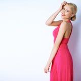 Herrliche blonde sexy Frau, die im rosa Kleid aufwirft Stockbild