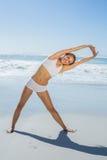 Herrliche blonde Stellung und Ausdehnen durch das Meer Lizenzfreies Stockfoto