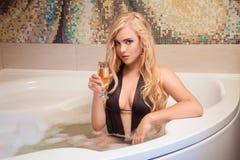 Herrliche Blondine im Bad mit Glas Champagner Stockbild