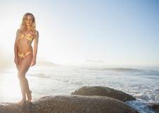 Herrliche Blondine im Bikini, der auf einem Felsen am Strand aufwirft Lizenzfreie Stockfotografie