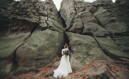Herrliche Braut, Bräutigam, der nahe den Klippen mit erstaunlichen Ansichten küsst und umarmt lizenzfreie stockbilder