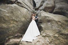 Herrliche Braut, Br?utigam, der nahe den Klippen mit erstaunlichen Ansichten k?sst und umarmt stockfotografie