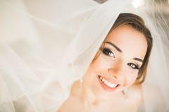 Herrliche Braut in der Robe, die für das Hochzeitszeremoniegesicht in einem Raum aufwirft und sich vorbereitet lizenzfreies stockfoto
