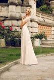 Herrliche Braut mit dem blonden Haar trägt luxuriöses Kleid und Zubehör lizenzfreie stockbilder