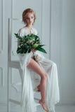 Herrliche Braut mit dem Hochzeitsblumenstrauß, der auf der verzierten Leiter sitzt Stockfotografie