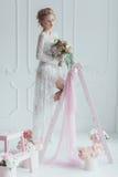 Herrliche Braut mit dem Hochzeitsblumenstrauß, der auf der verzierten Leiter steht Junge Frau schaut heraus das Fenster Stockbilder