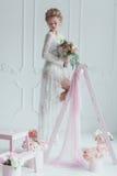 Herrliche Braut mit dem Hochzeitsblumenstrauß, der auf der verzierten Leiter steht Schauen Sie unten Stockfotos