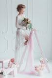 Herrliche Braut mit dem Hochzeitsblumenstrauß, der auf der verzierten Leiter steht Schauen Sie unten Stockfoto