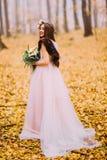 Herrliche Braut mit dem langem dunklen Haar und Kranz gehend auf die Späthölzer Lizenzfreies Stockfoto
