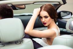 Herrliche Braut mit Modemake-up und -frisur in einem Luxushochzeitskleid mit hübschem Bräutigam nahe weißem Cabrioletauto stockbild