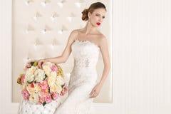 Herrliche Braut mit weißem Kleid mit Blumenblumenstrauß stockfotografie