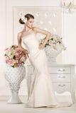 Herrliche Braut mit weißem Kleid mit Blumenblumenstrauß lizenzfreie stockbilder
