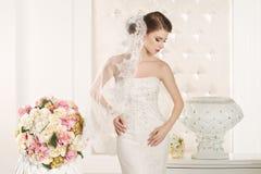 Herrliche Braut mit weißem Kleid mit Blumenblumenstrauß stockbilder