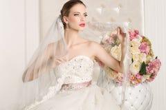 Herrliche Braut mit weißem Kleid mit Blumenblumenstrauß stockbild