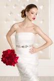 Herrliche Braut mit weißem Kleid mit Rot blüht Blumenstrauß stockbilder
