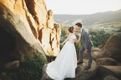 Herrliche Braut und stilvoller Bräutigam, die an der sonnigen Landschaft, Heiratspaar, Luxuszeremonieberge mit erstaunlicher Ansi stockbild