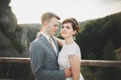 Herrliche Braut und stilvoller Bräutigam, die an der sonnigen Landschaft, Heiratspaar, Luxuszeremonieberge mit erstaunlicher Ansi lizenzfreie stockfotos