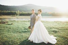 Herrliche Braut und stilvoller Bräutigam, die an der sonnigen Landschaft, Heiratspaar, Luxuszeremonieberge mit erstaunlicher Ansi lizenzfreie stockfotografie