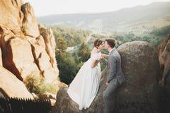 Herrliche Braut und stilvoller Bräutigam, die an der sonnigen Landschaft, Heiratspaar, Luxuszeremonieberge mit erstaunlicher Ansi stockfoto