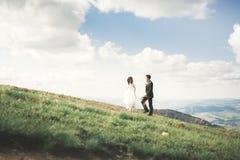Herrliche Braut und stilvoller Bräutigam, die an der sonnigen Landschaft, Heiratspaar, Luxuszeremonieberge mit erstaunlicher Ansi lizenzfreies stockfoto