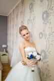 Herrliche Brautblondine im Hochzeitskleid im Luxusinnenraum, der zu Hause aufwerfen und in Wartebräutigam Romantische glückliche  Lizenzfreie Stockfotografie