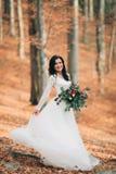 Herrliche Brunettebraut im eleganten Kleid, das den Blumenstrauß aufwirft nahe Wald und See hält stockfotos