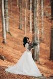 Herrliche Brunettebraut im eleganten Kleid, das den Blumenstrauß aufwirft nahe Wald und See hält stockfotografie