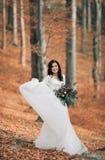 Herrliche Brunettebraut im eleganten Kleid, das den Blumenstrauß aufwirft nahe Wald und See hält lizenzfreie stockfotos